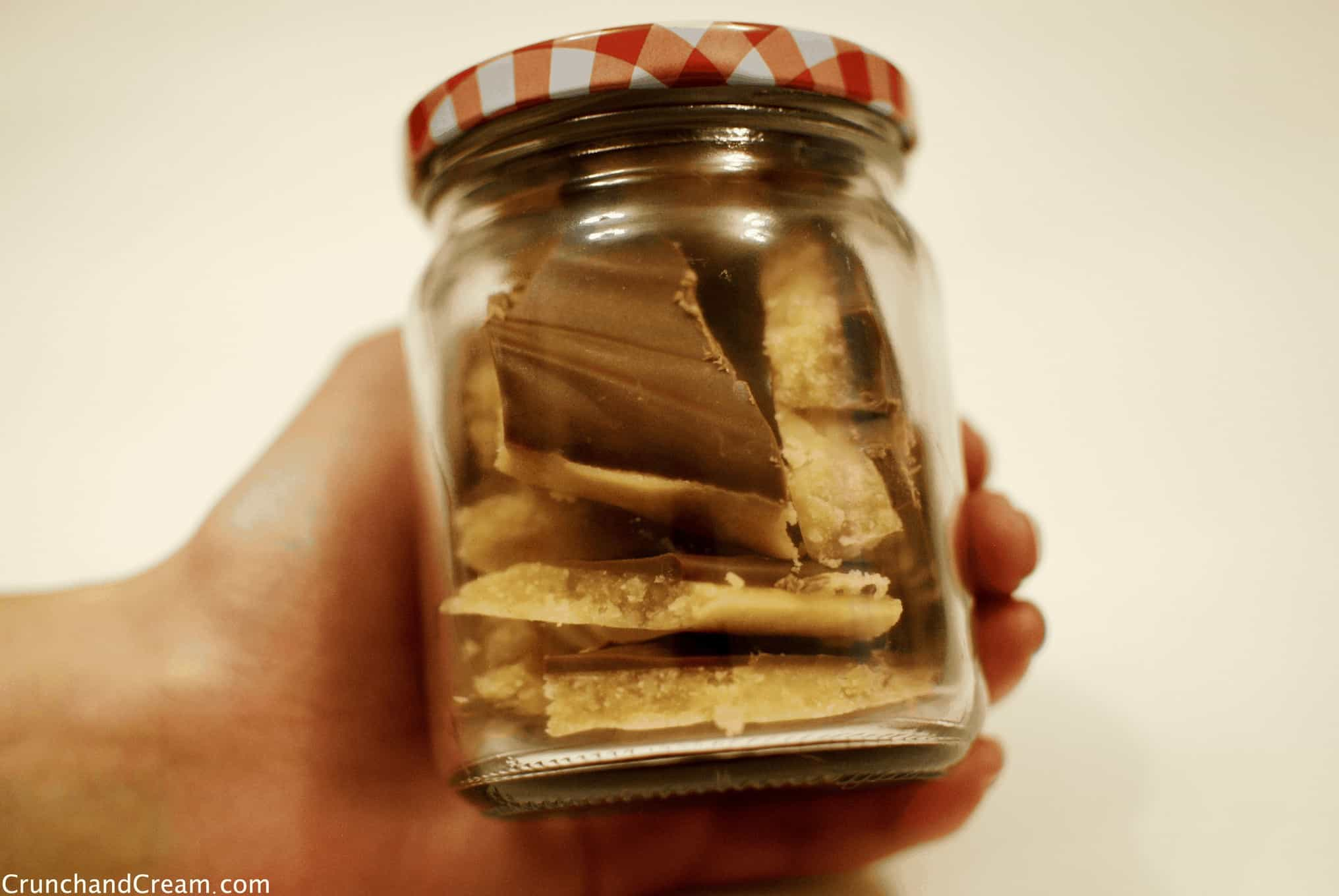 Hand holding a glass mason jar jar full of shards of caramel topped with a thin layer of milk chocolate.