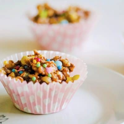 chocolate rice krispie cupcake on a plate with more cakes behind it and a white background.