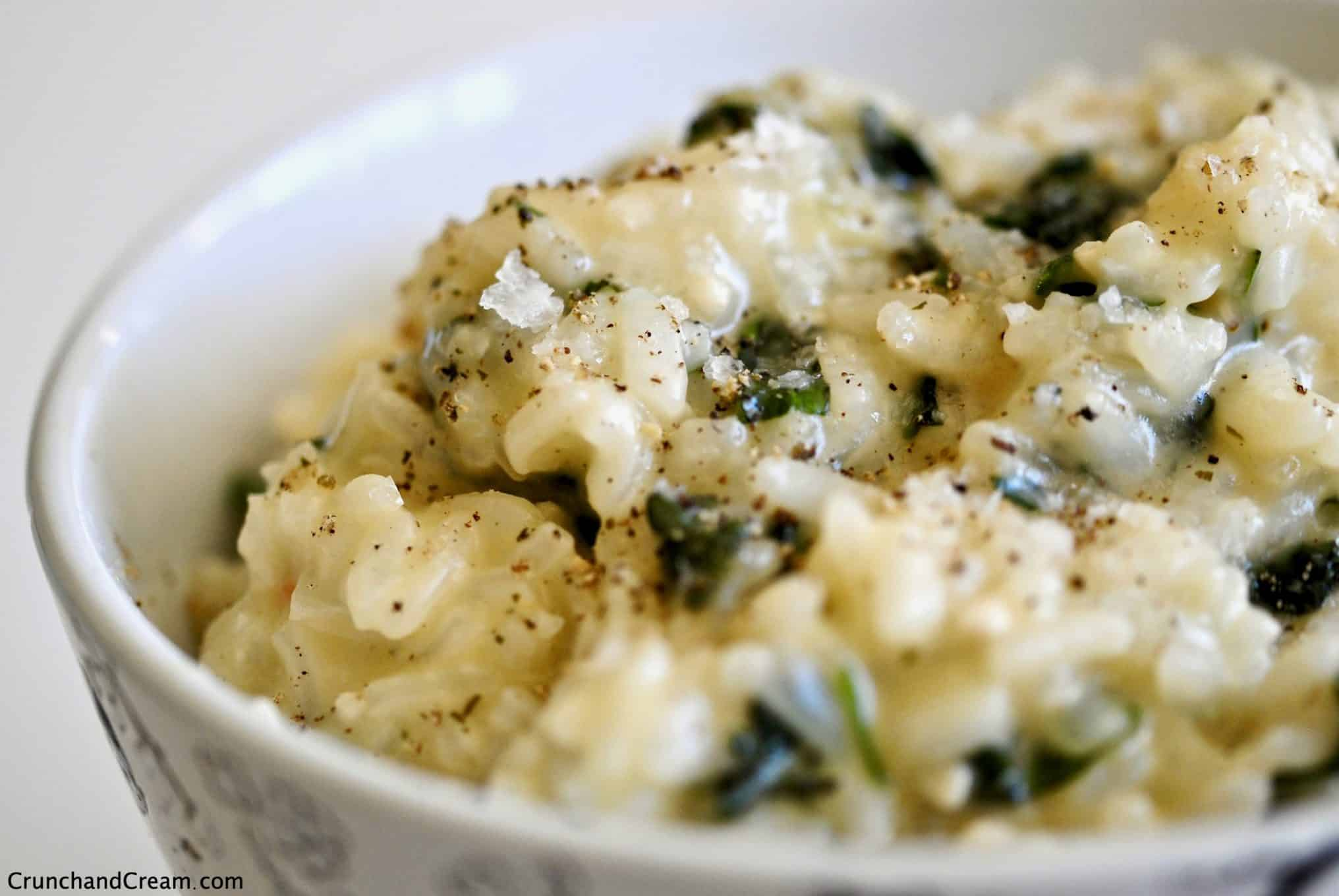 A close-up of a bowl full of creamy risotto with chopped green herbs in.