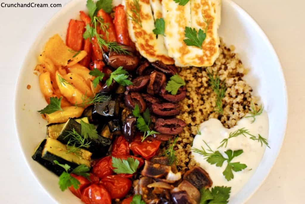 A deliciously healthy vegetarian bowl full of quinoa, halloumi and roasted peppers, tomatoes, courgette, aubergine and onion, with dill, parsley, a drizzle of lemon-garlic yogurt and a handful of black olives. The perfect comforting warm dinner for anyone health-conscious!