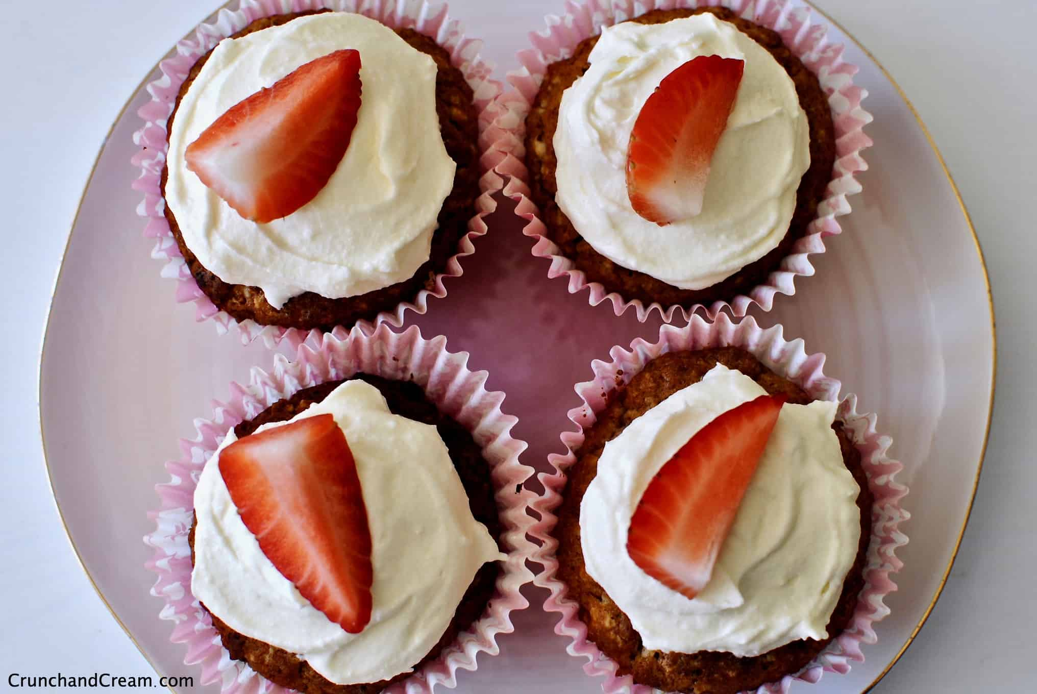 Overhead photo of 4 strawberry cupcakes topped with white chocolate cream cheese frosting and strawberry slices on a pale pink plate.
