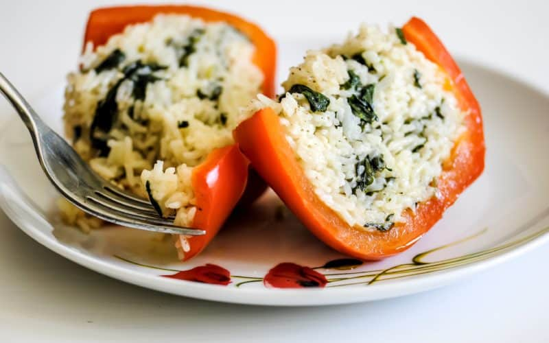halved stuffed pepper on a plate full of cheesy basil and spinach rice. A fork is taking a bite-size piece of the pepper.