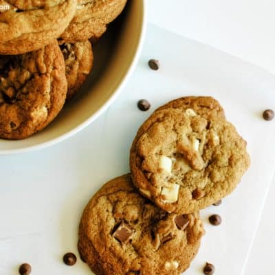 overhead of several chewy cookies laid out on parchment paper on a white background with parchment paper, scattered chocolate chips and a bowl containing more cookies