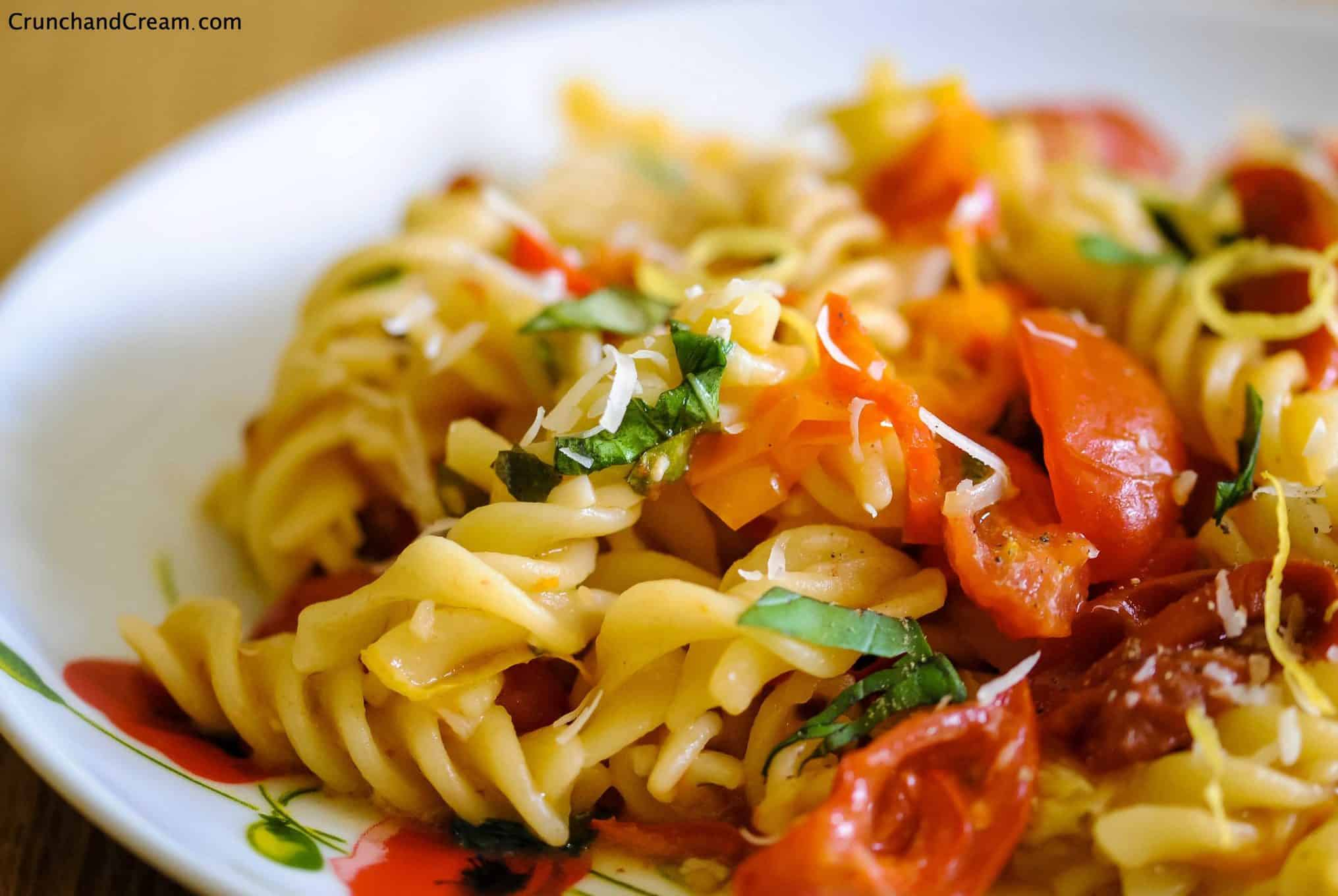 close-up eye-level photo of a plate of fusilli pasta cooked with fresh tomatoes and chilli peppers, topped with lemon zest and chopped fresh herbs