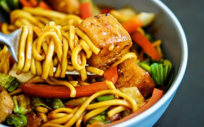close-up of a bowl of fresh egg noodles, red bell pepper, pak choi and spring onions with crispy diced halloumi pieces in a spicy sweet chilli sauce with noodles wound around a fork