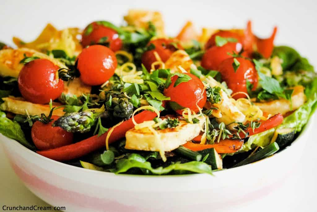 bowl of halloumi salad with halloumi slices, grilled tomatoes and peppers, lettuce, lemon zest and herbs