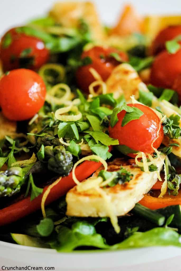 close-up of halloumi salad with grilled tomatoes and peppers as well as lettuce, herbs and lemon zest