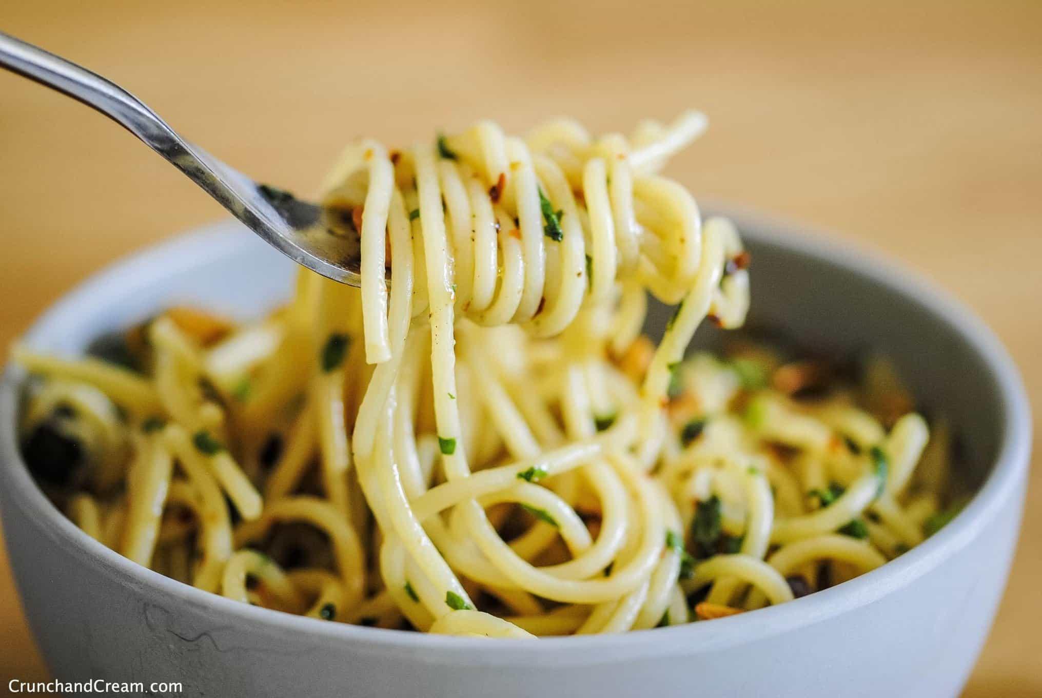 simple garlic basil pasta (spaghetti) wound around a fork