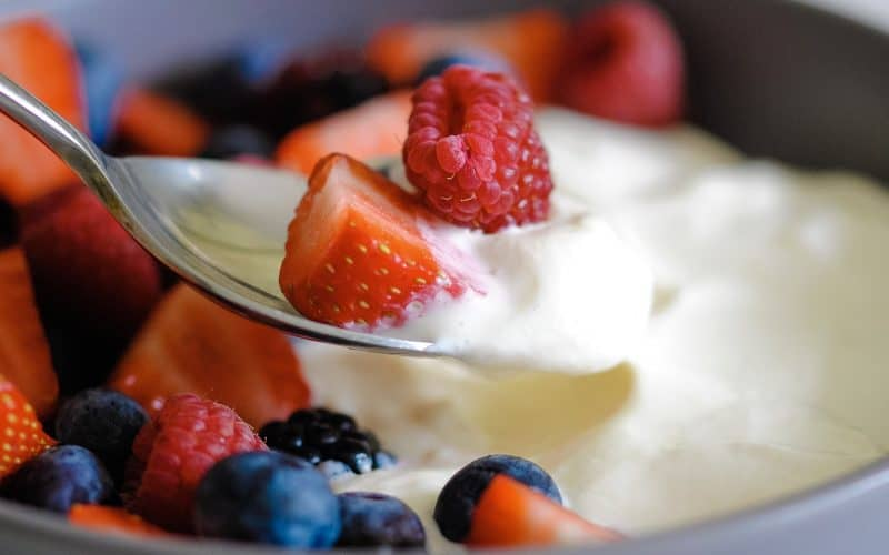 a spoon holding fresh berries and creamy cheesecake mix, with more of both in a bowl in the background