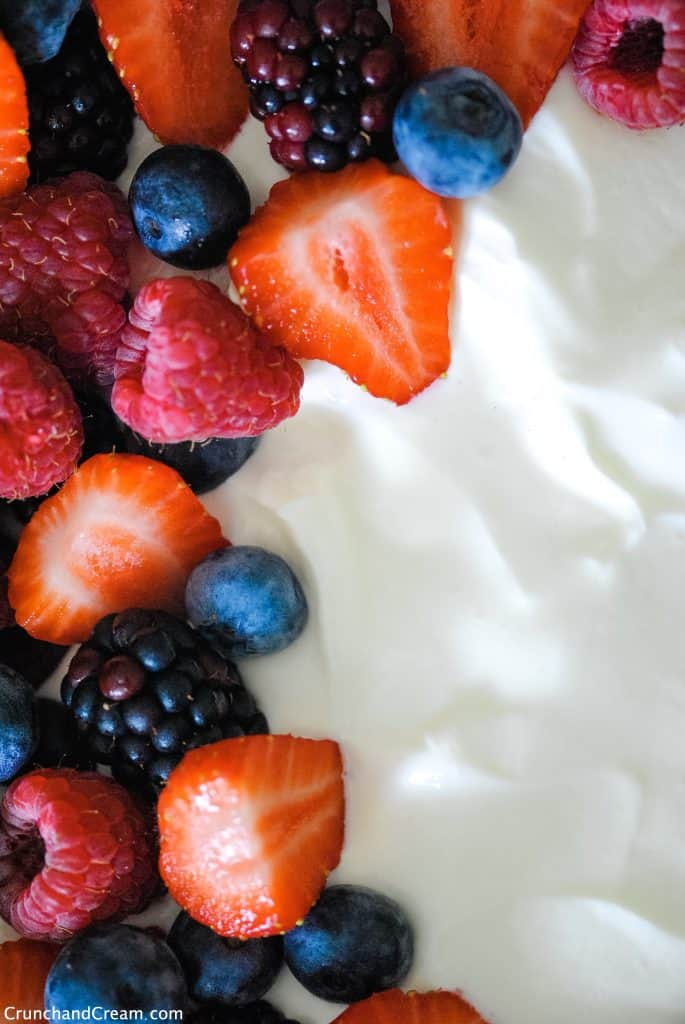 close up with one side of mixed fresh berries and the other as white cheesecake mixture