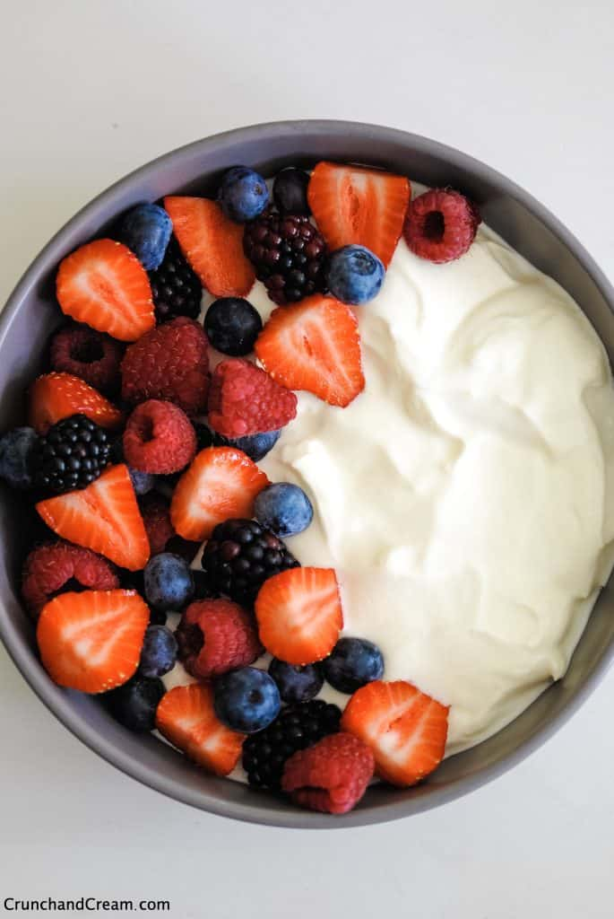 overhead photo of a bowl with mixed fresh berries on one side and cheesecake mix on the other