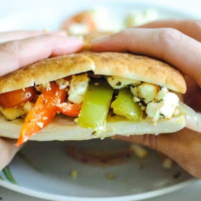 hands holding a bread roll filled with peppers, tomatoes, onions and feta