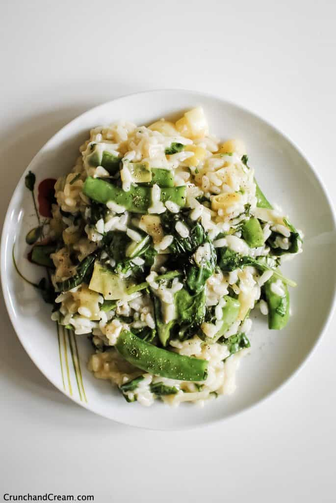 a plate of green vegetable risotto with spinach, sugar snap peas, leeks and herbs