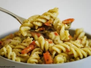 a fork full of a bowl of pesto pasta with diced red pepper