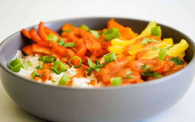 A bowl of rice and colourful vegetables drizzled with red enchilada sauce