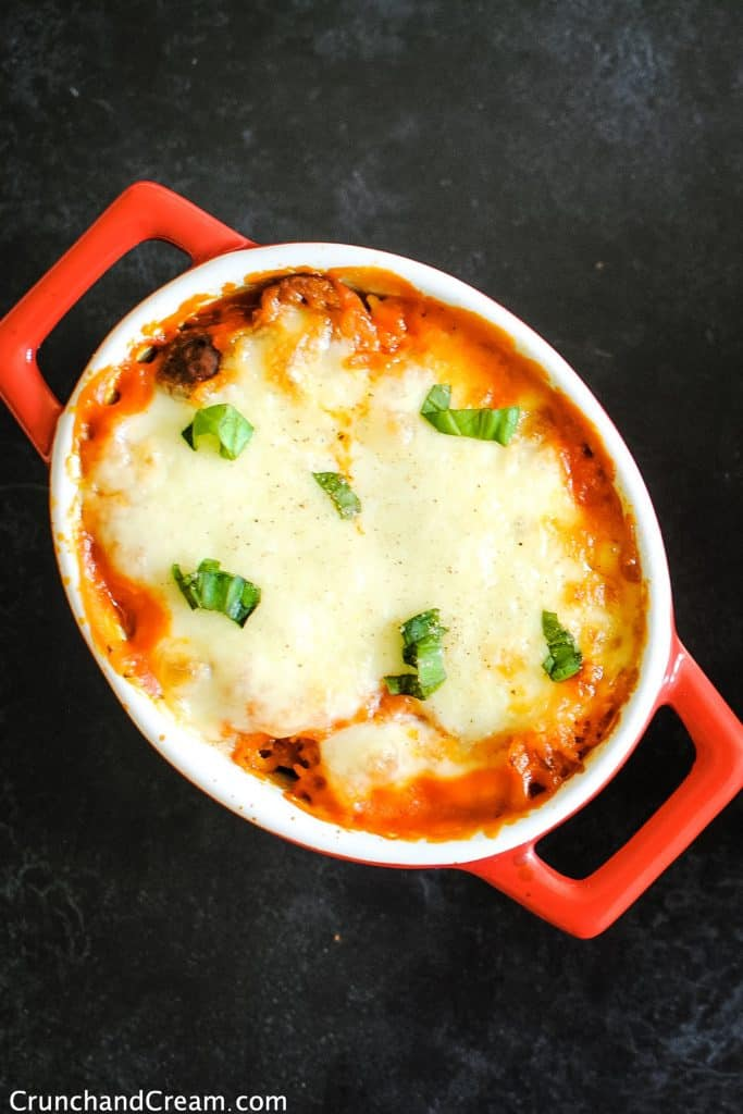 overhead of a casserole dish full of baked rice in a tomato sauce topped with melted cheese