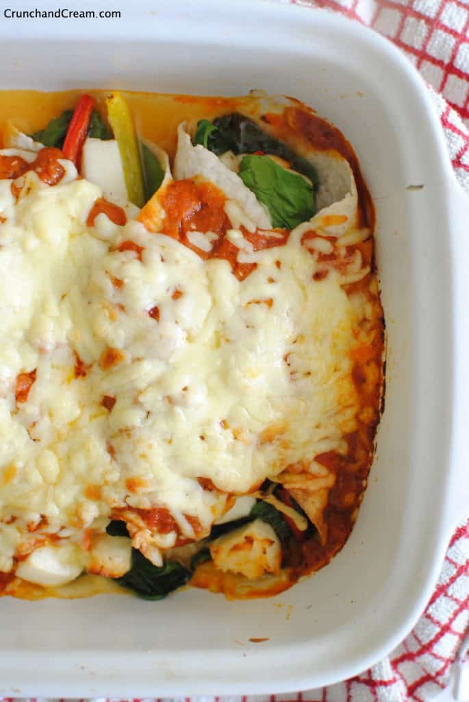 close-up of the ends of the enchiladas covered in sauce and cheese and filled with halloumi, peppers and spinach