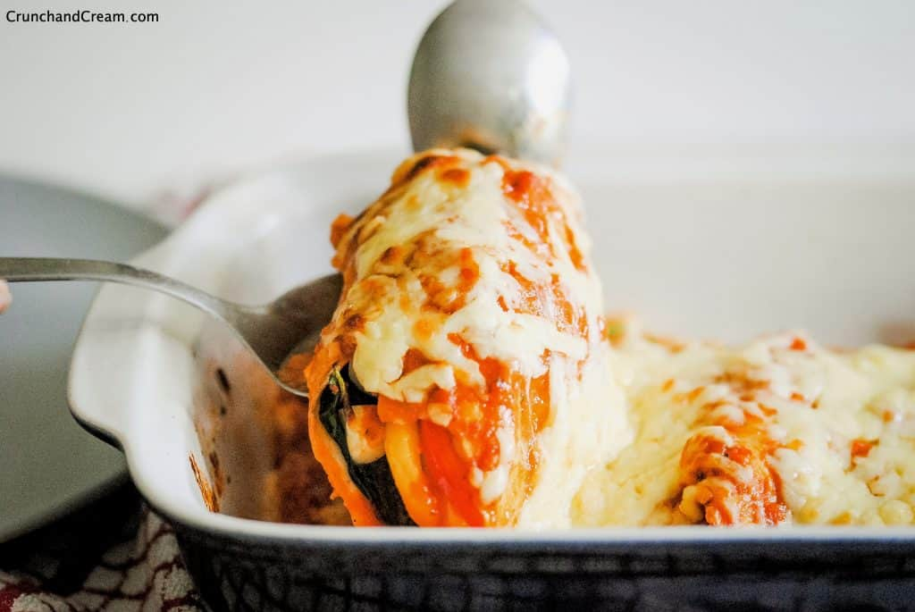 serving spoon lifting an enchilada covered in sauce and cheese out of the baking dish