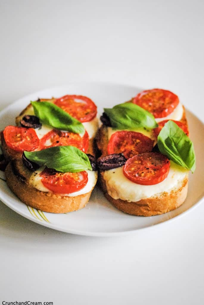 two slices of toast with cheese, tomatoes, olives and basil