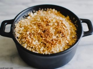a small round dish of apple crumble with a golden, crispy topping