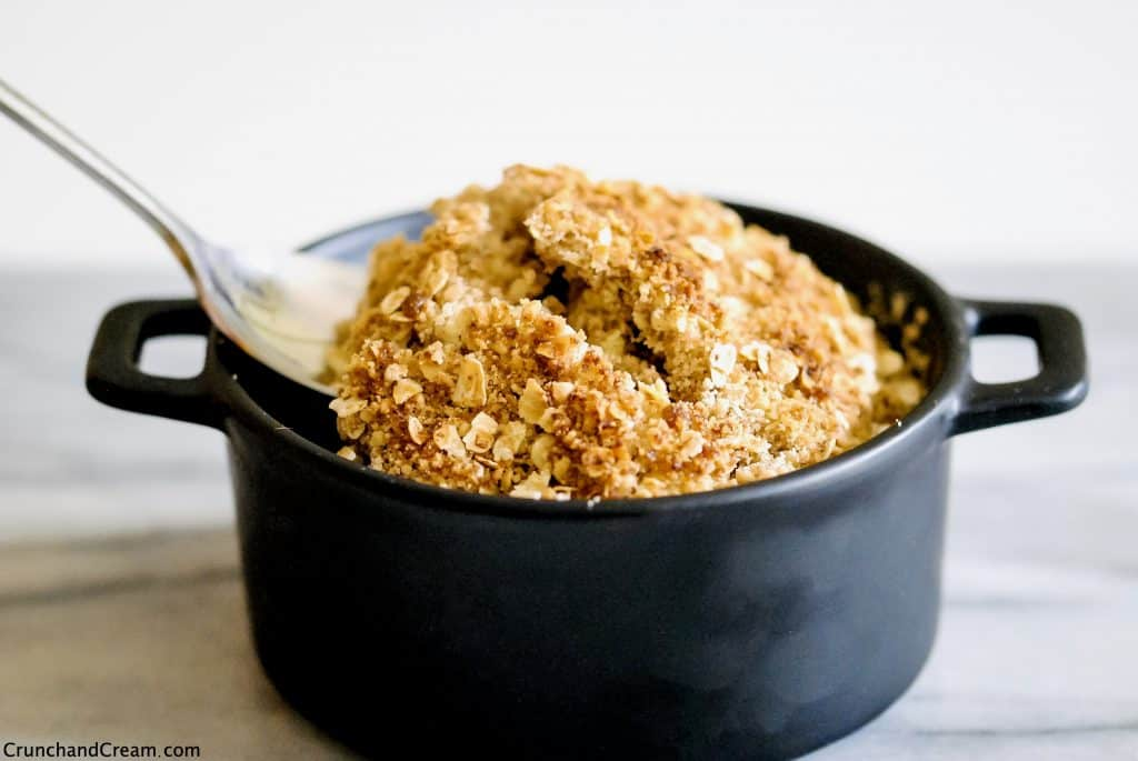 a spoon digging in to a dish of apple crumble with cracks in the crispy topping