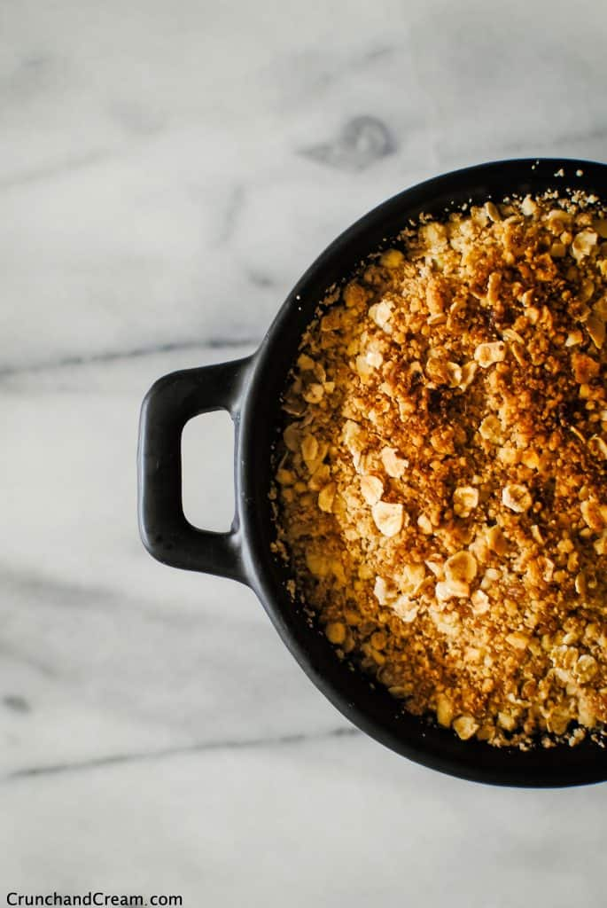 close-up overhead of a round, black dish of apple crumble with a crispy, golden-brown topping