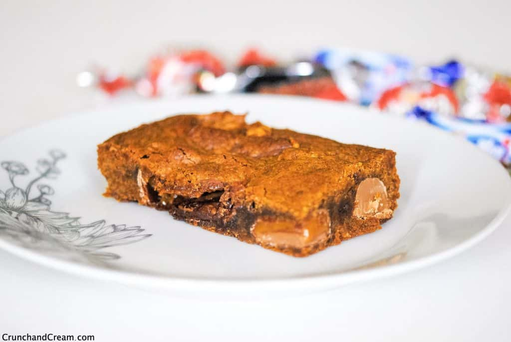 a blondie stuffed with mini chocolate bars on a plate