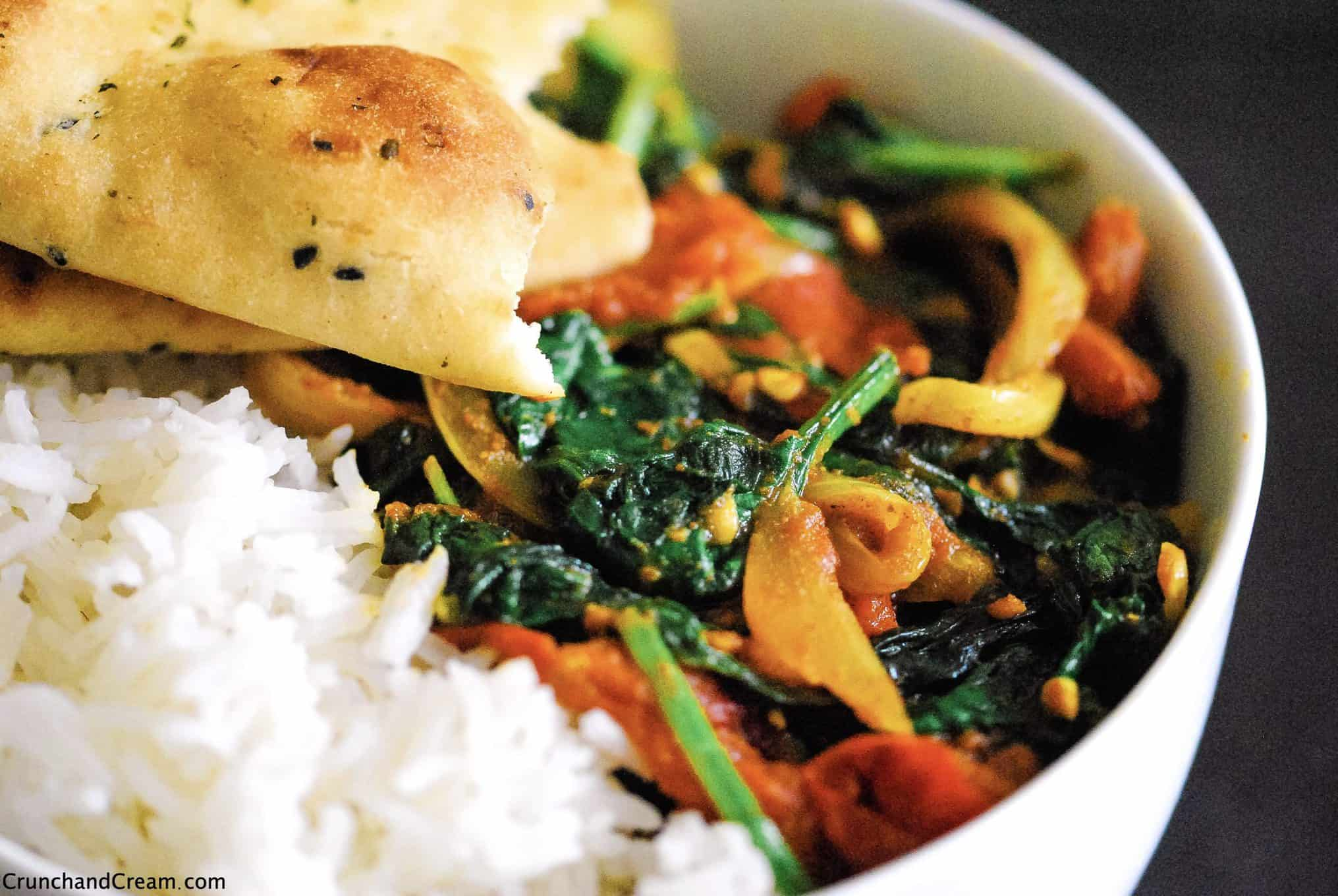 a close-up shot of a vegetable masala curry in a bowl with spinach, onions and tomatoes. Served with basmati rice and a torn naan bread.
