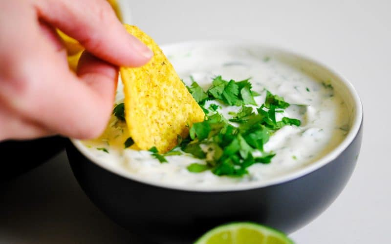 someone dunking a tortilla chip into a bowl of coriander lime dipping sauce