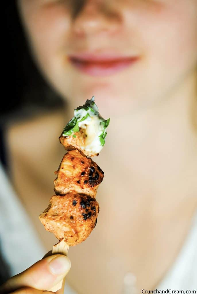 a woman about to eat a grilled taco chicken skewer