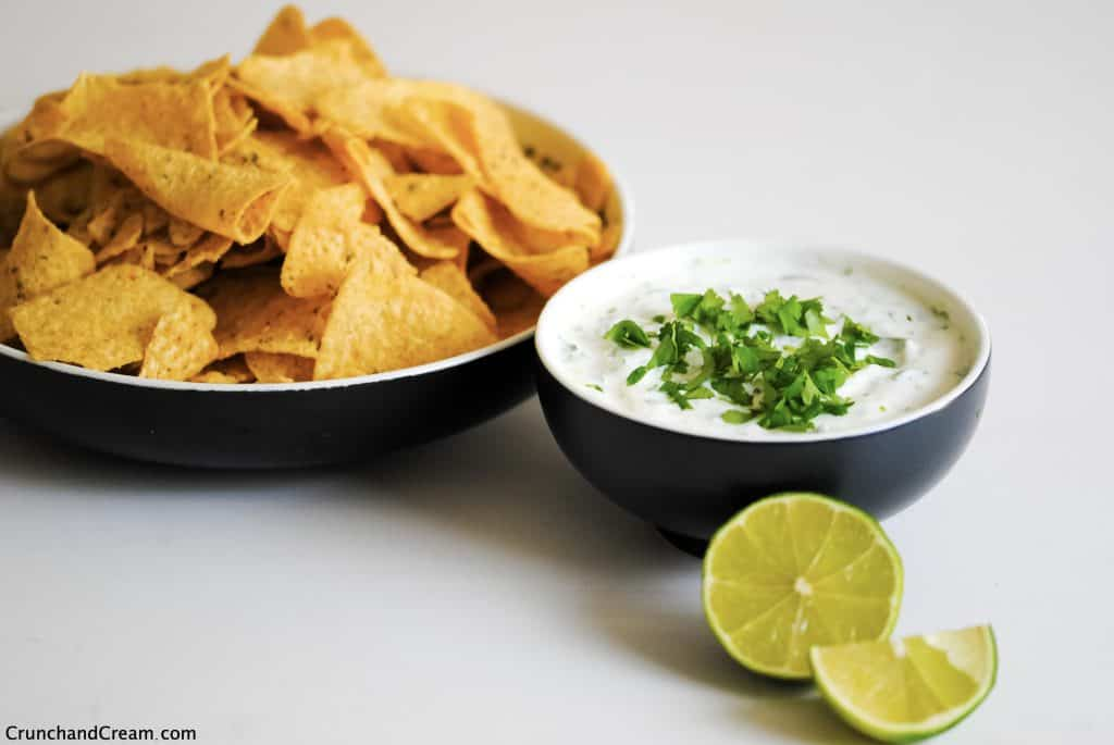 a bowl of coriander lime dipping sauce with a sliced lime and a bowl of tortilla chips
