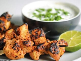 a pile of taco spiced grilled chicken on skewers in front of a coriander dipping sauce and half a lime