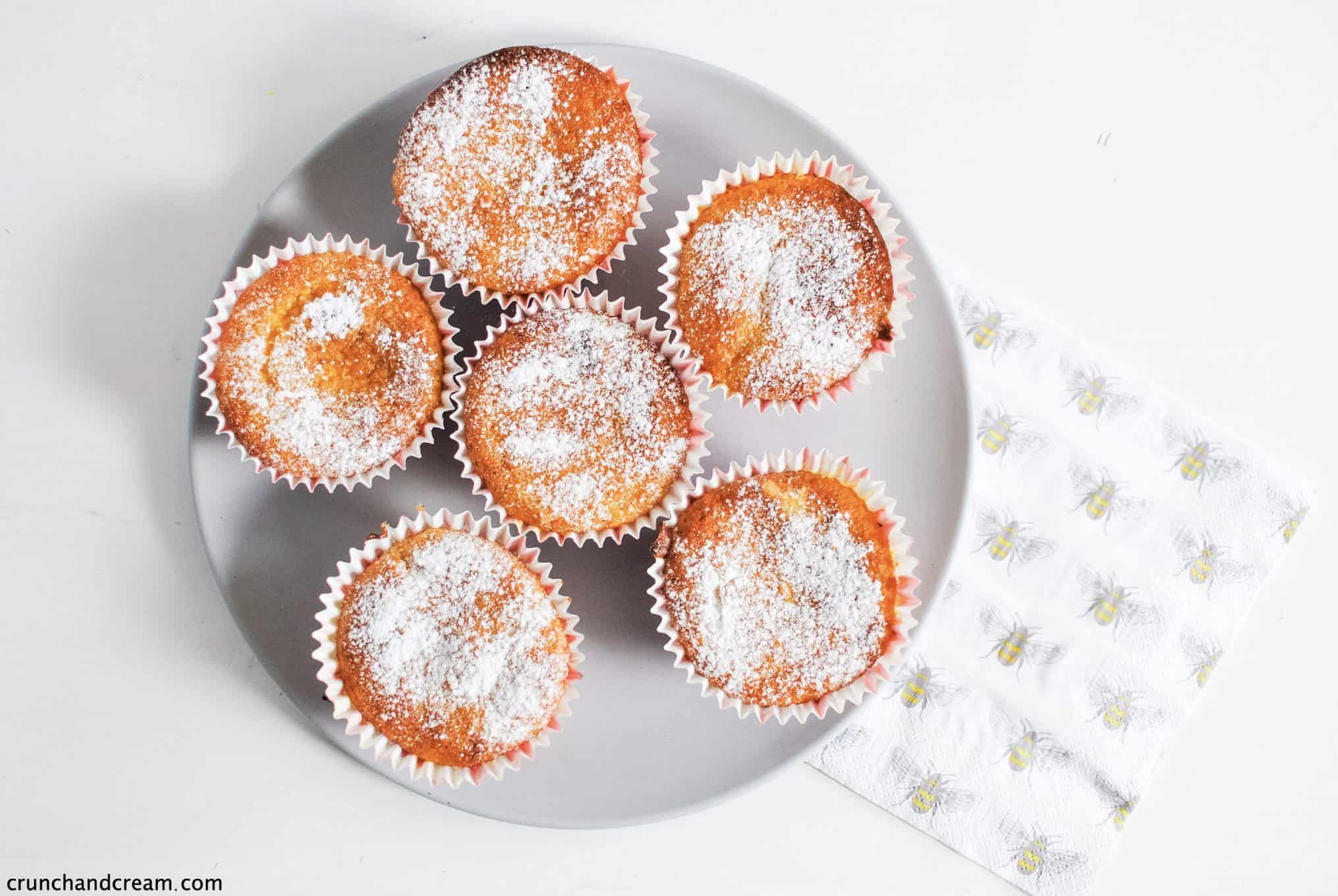 a plate of citrus olive oil cupcakes with a napkin to the side