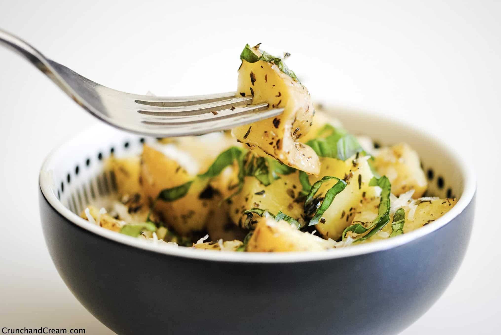 eye-level view of diced cooked potatoes in a bowl with grated cheese and chopped herbs. A fork is holding one piece of potato.