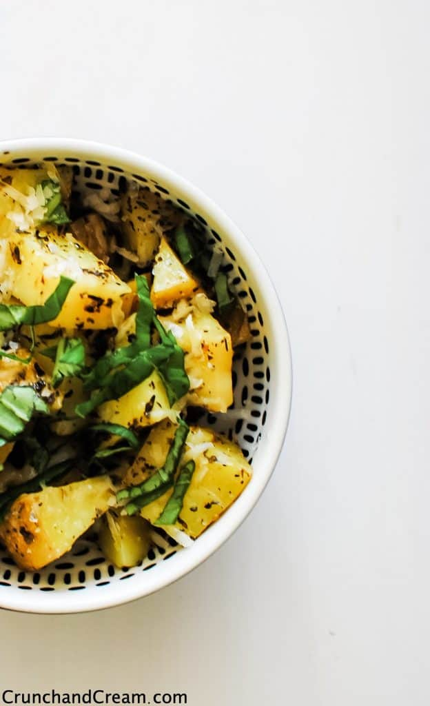 Overhead of a bowl full of yellow potatoes topped with grated cheese and fresh herbs.