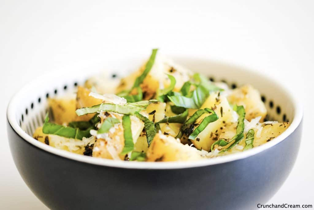 eye-level view of diced cooked potatoes in a bowl with grated cheese and chopped herbs