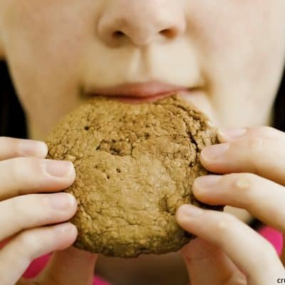 a young girl about to take a bite of a brown nutella cookie