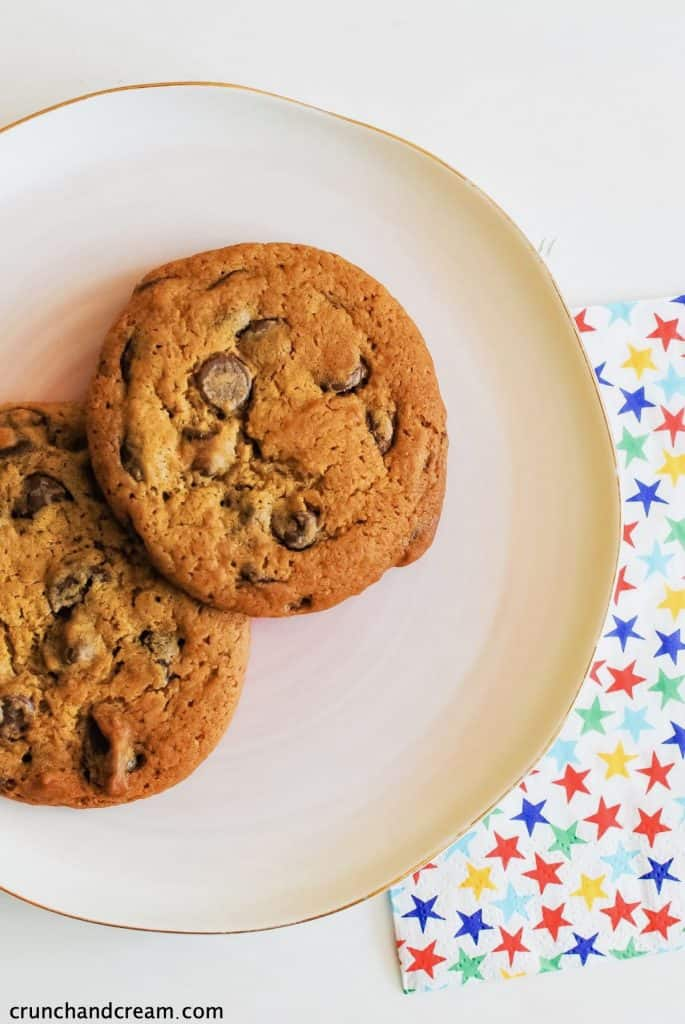 overhead of 2 chocolate chip cookies on a plate with a starry napkin