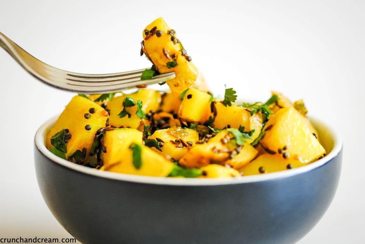 A bowl of yellow potatoes with fresh coriander and spices. A fork is holding one piece of potato.