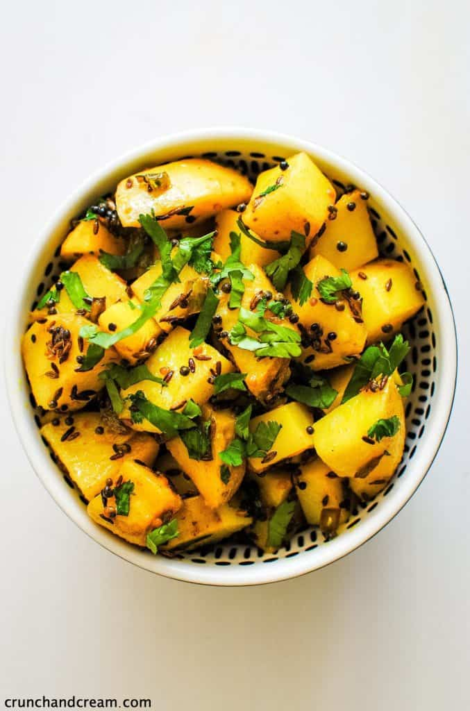 overhead of a black bowl full of yellow spiced cubes of potato
