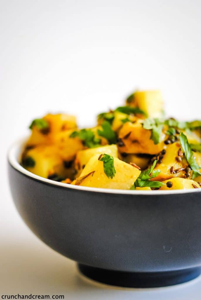 a black bowl of yellow spiced potatoes topped with fresh green herbs