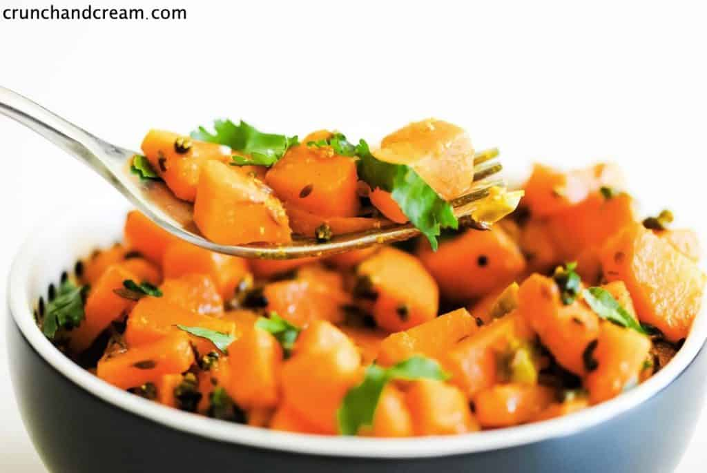 fork holding diced carrot coated with spices