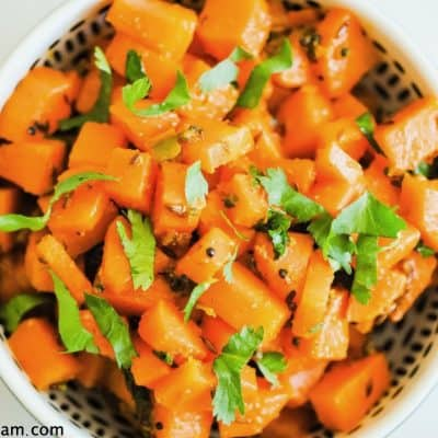 bowl of carrot pieces (overhead) with some fresh herbs and small whole spices