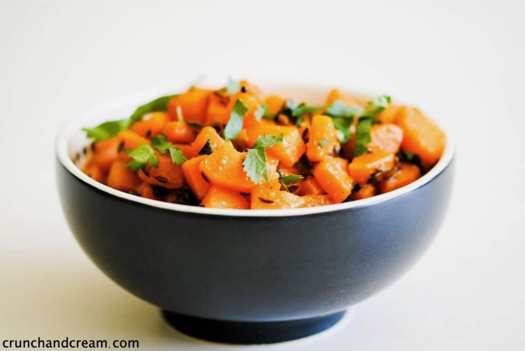 bowl of diced carrots with some fresh herbs and spices
