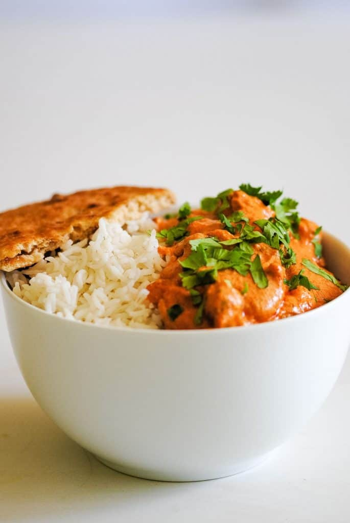 bowl of rice and orange curry sauce with a naan bread