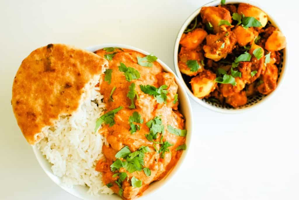bowl of rice and orange curry sauce and a potato side dish