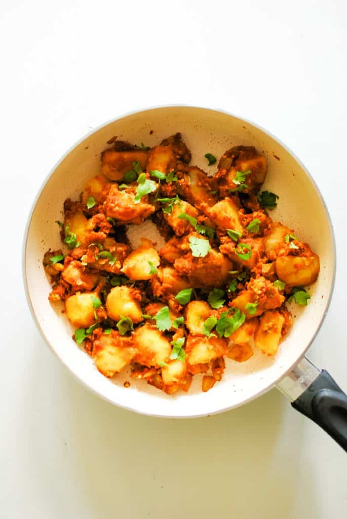 frying pan full of potatoes in a red sauce