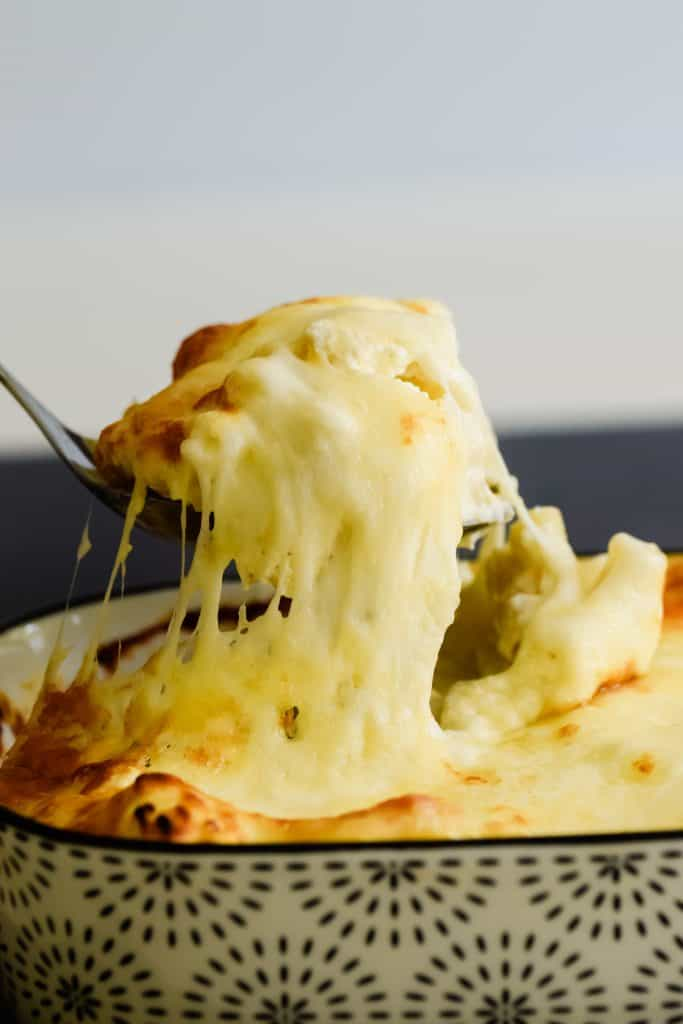 serving a portion of macaroni cheese covered in melted cheese