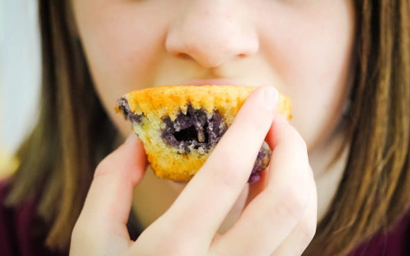 young girl eating blueberry cupcake